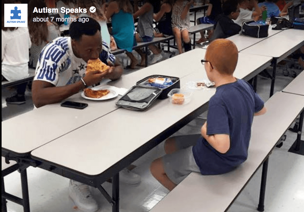 college basketball player eats lunch with autistic boy